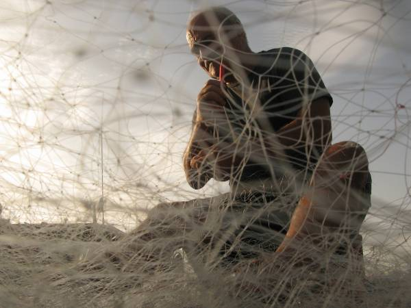 Pescatore che ripara la rete nel porto di Golfo Aranci